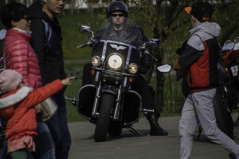 Motorkár celý v čiernom, diváci, otvorená moto-prilba
