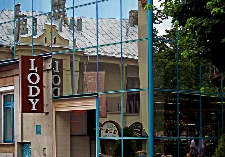 Budova so sklenenými stenami v ktorých sa odráža mesto.jpg
