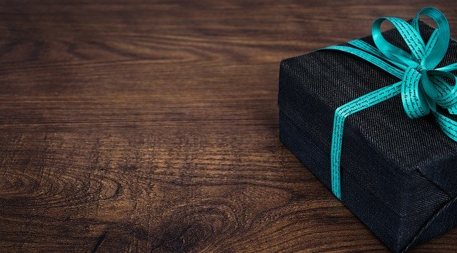 Čierna krabička s modrou stuhou – darček, na drevenom stole.jpg