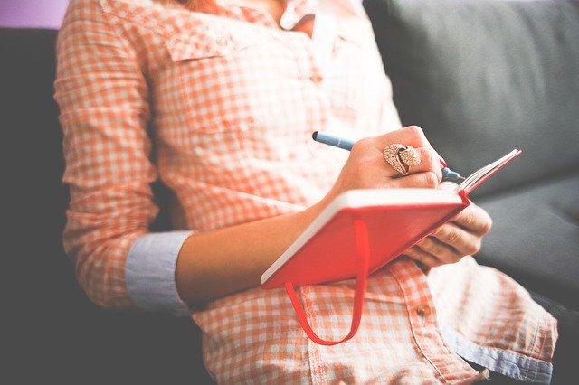 Žena v kockovanej oranžovej košeli píše do zápisníka.jpg