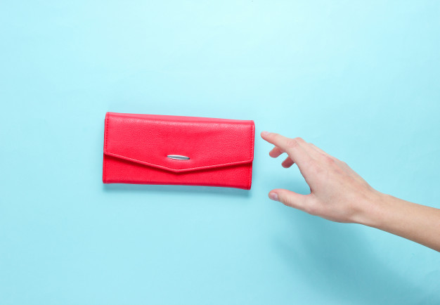 minimalism-trend-female-hand-takes-red-leather-wallet-blue-background-top-view_175682-3136
